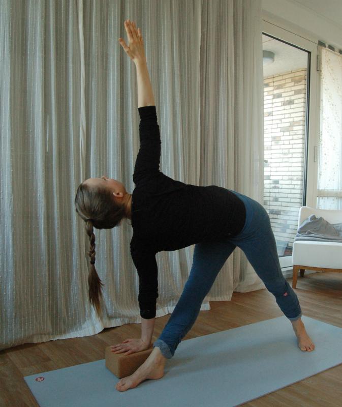 yoga staande houding parivrtta trikonasana met kurkblok ter ondersteuning