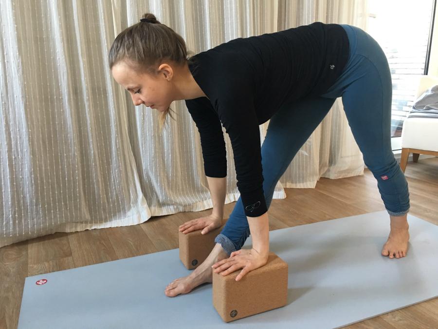 yoga staande houding vooroverbuigen parsvottanasana met handen op blokken