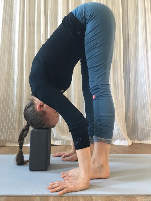 yoga vooroverbuiging uttanasana met hoofd steunend op blok restoratief oefenen